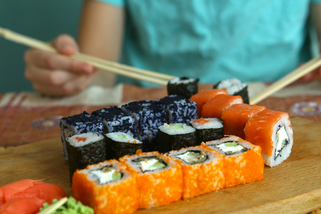 hands with japanese chopsticks and suchi rolls close up photo