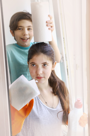 office cleanup: teen girl with brother boy in orange rubber gloves cleaning window close up portrait