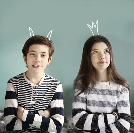 teenager brother and sister with demon horns and princess crown drowing close up photo Stock Photo