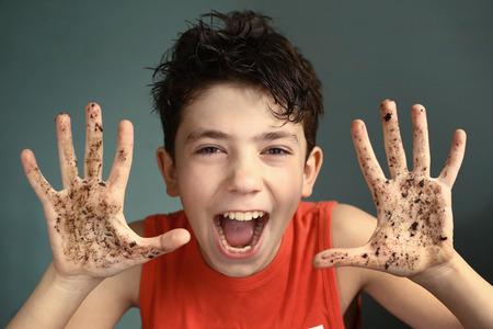 Preteen ondeugende jongen met vieze handen open mond lachende portret