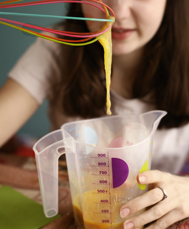 teenager girl mix raw eggs in measure jar close up photo