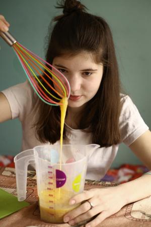 Tiener meisje mix rauwe eieren in maat pot close-up foto Stockfoto