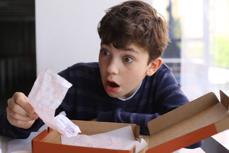 embarassment: teenager boy shocked expression after see bill for pizza in fast food restaurant