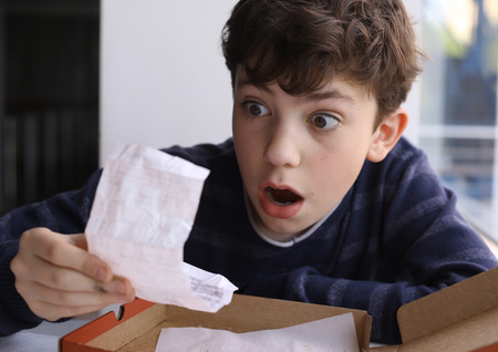 payable: teenager boy shocked expression after see bill for pizza in fast food restaurant