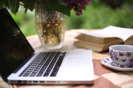 laptop with open book and tea cup  and lilac bouquet in vase on summer garden background