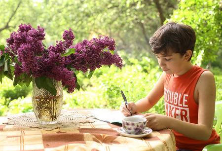 teenager boy make homework school on summer holiday in green garden