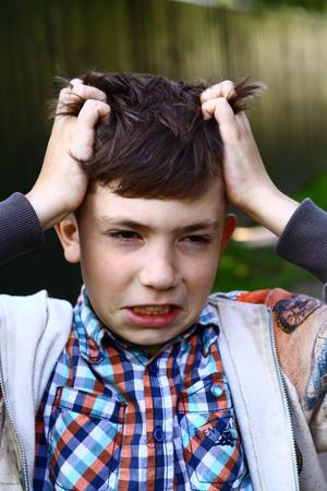 piojos: niño con piojos picazón cabeza scratch close up verano al aire libre photo
