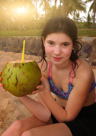 teen girl hold coconut with cut top and straw close up photo Stock Photo