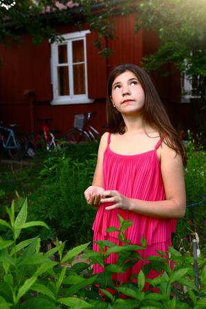 pubertad: niña adolescente con el pelo largo y castaño en vestido rosa foto de cerca en el jardín de verano verde en el fondo de la casa de campo Foto de archivo