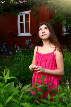 teen girl with long brown hair in pink dress close up photo in summer  green garden on country house background