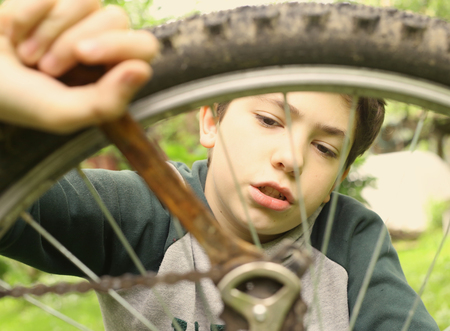 self sufficient: teen boy repair bicycle tire close up summer photo