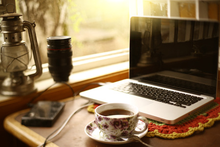 country still life composition with laptop, teacup, oil lamp, window on the table