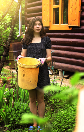 80924515 teenager girl work in the garden with yellow plastic bin on country house background