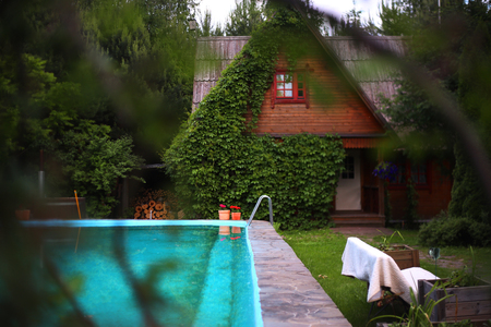 a bathing place: country summer house with ivy with swimming pool close up photo Stock Photo