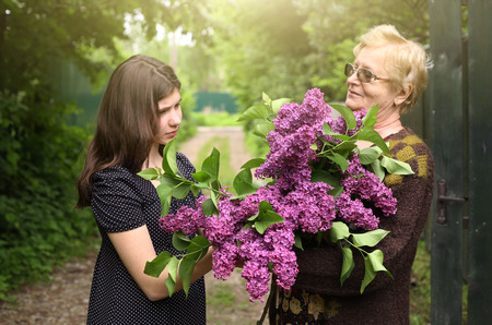 the grand daughter: grandma and grand daughter with lilac bouquet close up summer outdoor photo