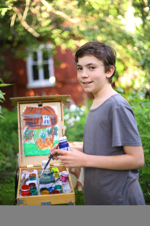 teenager artist  boy in garden painting picture of jasmin flowers and cottage house composition Stock Photo