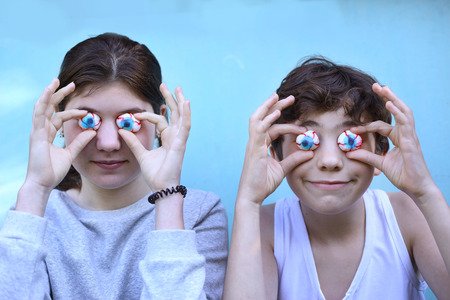 marshmellow: teenager boy and girl with jujube marshmellow eyes smiling open mouth close up portrait Stock Photo