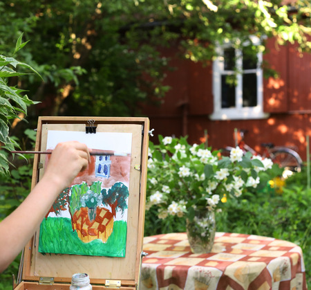 artist hand painting picture of jasmin flowers and cottage house composition in summer garden