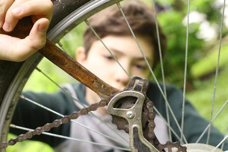 teen boy repair bicycle tire close up summer photo
