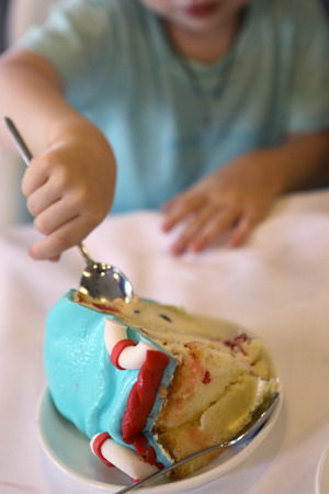 piece of birthday kids cake cut on the plate with teaspoon in kid hands eating close up photo Stock Photo