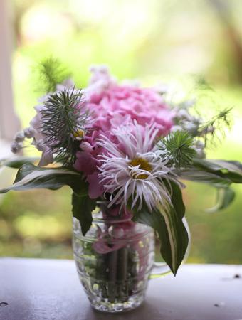 cute mini hydrangea bouquet in beer mug stay on the windowsill on the green garden background