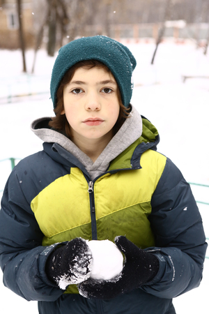 teenager modeling snow ball close up photo on winter snowy background Stock Photo