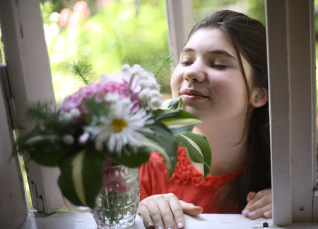 teenager girl with hydrangea boupuet close up photo on summer green background
