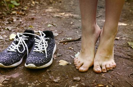 blote voeten blijven tiptoe en trainer schoenen close-up foto op het bospad