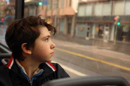 teenager boy in the bus looking at the window close up photo