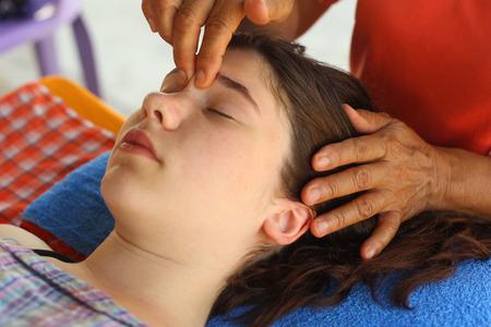tête visage massage thai adolescent fille aux yeux fermés et massage des mains bouchent photo en plein air