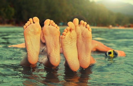 kids teenager feet close up photo in the sea on the tropical beach background