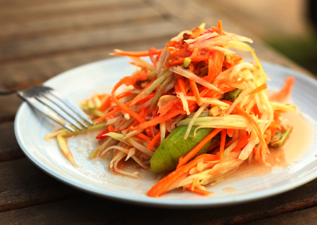 spicy papaya salad traditional thai dish served with fork in outdoor street cafe close up photo