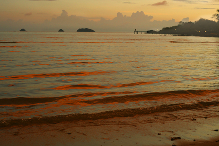 colorful pastes sunset on thai island with sea waves and hill on the horizon line