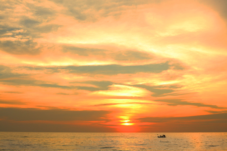 dramatic colorful sea sunset with sun setting on water lonely boat on horison and dark waves on foreground