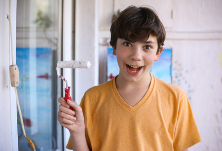 Smiling teenager boy with white paint roller and dirty face make repaint close up photo