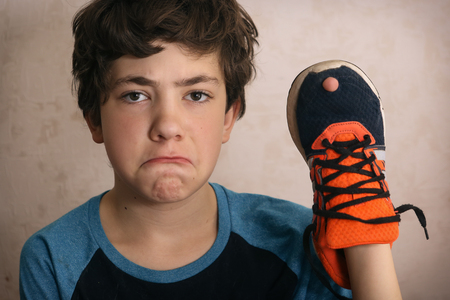 Teenager boy frustrated about hole in his favorite trainers shoes close up portrait Фото со стока