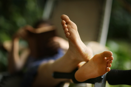 bare feet close up photo with book reading girl on deck chair on background Foto de archivo