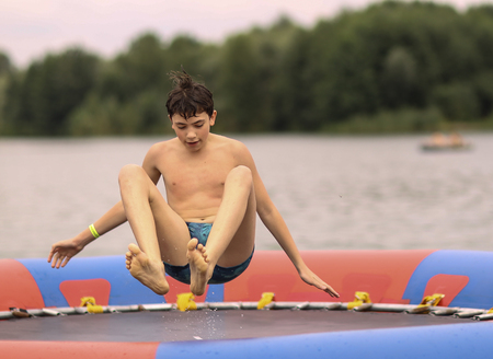 teenager boy in open air amusement aquapark jump on trampoline close up photo on lake background