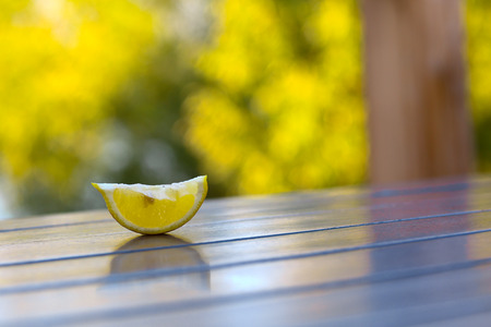 cut lemon pieve on wooden cafe table on green summer background horizontal photo