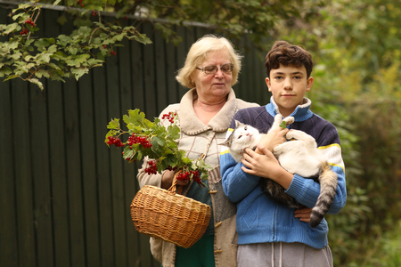 grandmother with grandson with viburnum and cat close up photo on green garden background