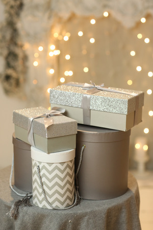 chriatmas silver gift boxes with garlandas lights on background