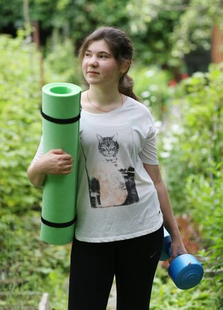 teenager girl with gym rag and dumbbell going to train exercises on green garden background Banco de Imagens - 127679366