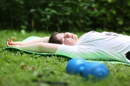 teenager girl lay exhausted on gym rag with dumbbell after train exercises on green garden background Banco de Imagens - 127679393