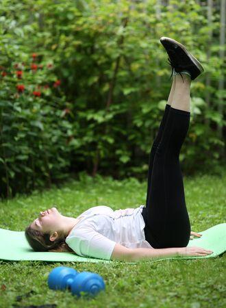 teenager girl lift legs make exercises for flat stomack with dumbbell on green garden background Banco de Imagens - 127679548