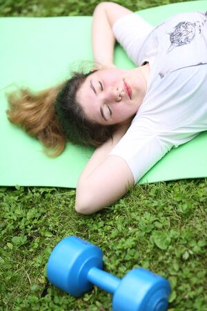 teenager girl lay exhausted on gym rag with dumbbell after train exercises on green garden background Banco de Imagens - 127679558