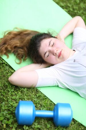 teenager girl lay exhausted on gym rag with dumbbell after train exercises on green garden background Banco de Imagens - 127679560