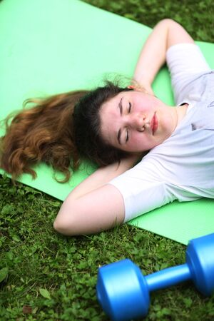 teenager girl lay exhausted on gym rag with dumbbell after train exercises on green garden background Banco de Imagens