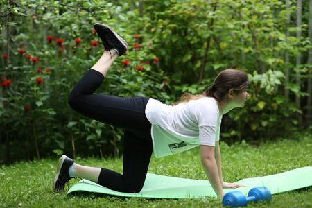 teenager girl lift legs make exercises for flat stomack with dumbbell on green garden background Banco de Imagens - 127679687
