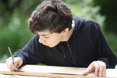 teenager boy carpenter measure wood board to make housekeeping work outdoor summer photo