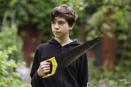 teenager boy with saw going to do housekeeping job close up photo on green garden background Banco de Imagens